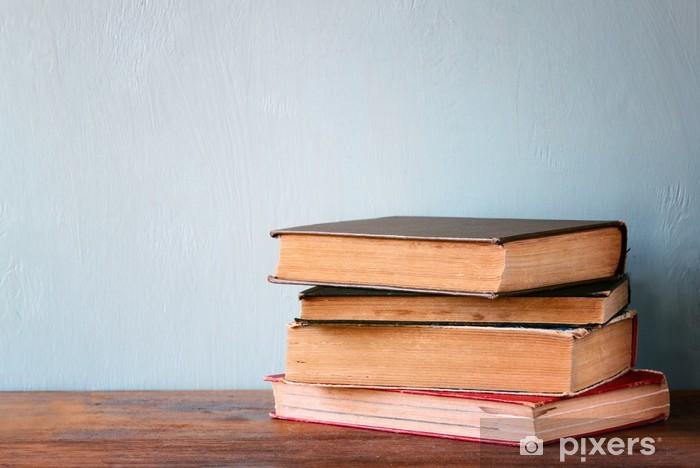 Vinyl Fotobehang Oude boeken op een houten tafel. retro gefilterde afbeelding - Onderwijs