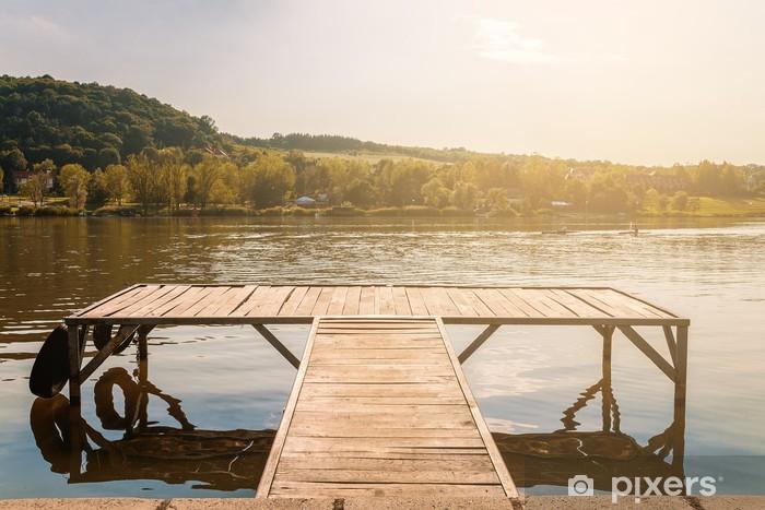 Fototapeta winylowa Molo w zachód słońca nad jeziorem. odbicie drzew w jeziorze. - Pory roku