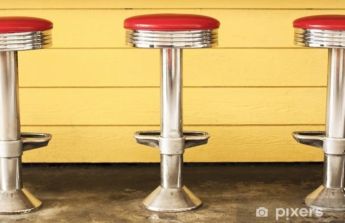 Fototapeta zmywalna Trzy retro chromowane stołki. czerwone siedzenia winylowe, żółte tło - Budynki i architektura