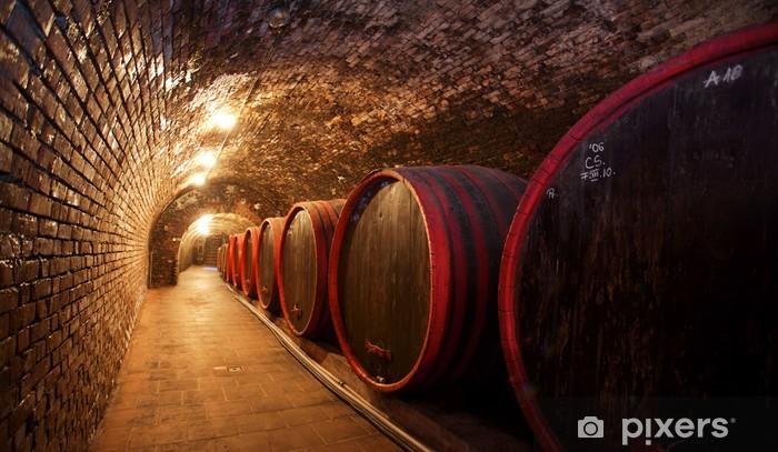 Fototapeta winylowa Beczki do wina ułożone w starej piwnicy z winnicy. - Alkohol