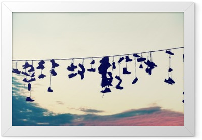 Retro stylized silhouettes of shoes hanging on cable at sunset, teenage rebellion concept. Framed Poster