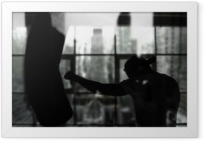 Boxer hits a punching bag against the window, training Framed Poster