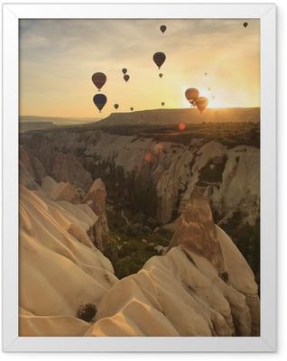 Hot air balloon over rock formations in Cappadocia, Turkey Framed Poster