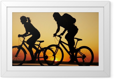 Young couple riding bicycles at sunset Framed Poster