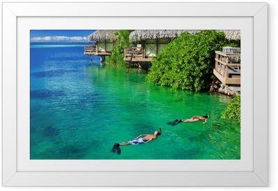 Poster i Ram Unga par snorkling i rent vatten över revet