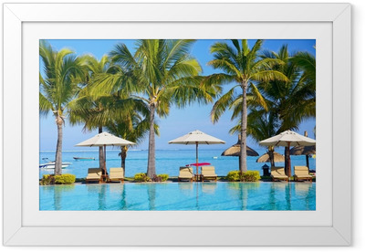 Swimming pool with umbrellas on beach in Mauritius Framed Poster