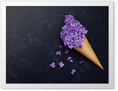 Ice cream of lilac flowers in waffle cone on black background from above, beautiful floral arrangement, vintage color, flat lay styling Framed Poster