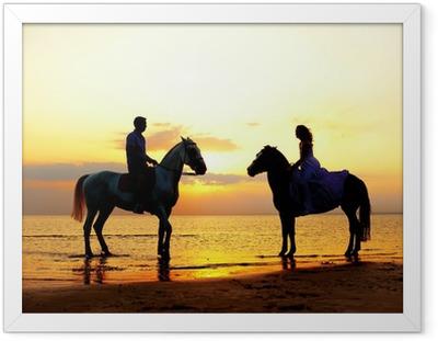 Poster in Cornice Due cavalieri a cavallo al tramonto sulla spiaggia. Gli amanti cavalcano hors