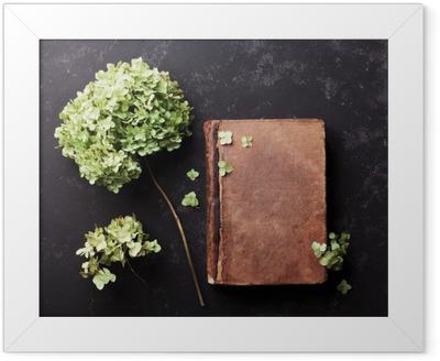 Stilleben med gammel bog og tørrede blomster hortensia på sort vintage bordet top view. Flad lay styling. Indrammet plakat
