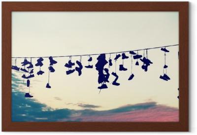 Plakát v rámu Retro stylizované siluety obuvi visí na kabelu při západu slunce, dospívání povstání konceptu.