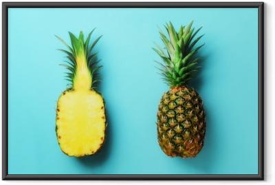 Gerahmtes Poster Ganze Ananas und Hälfte geschnittene Früchte auf blauem Hintergrund. Draufsicht kopieren sie platz. helles Ananasmuster für minimalen Stil. Pop-Art-Design, kreatives Konzept