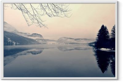 Ingelijste Poster Snowy winter landschap op het meer in zwart-wit. Zwart-wit beeld gefilterd in retro, vintage stijl met soft focus, rode filter en wat lawaai; nostalgische concept van de winter. Lake Bohinj, Slovenië.