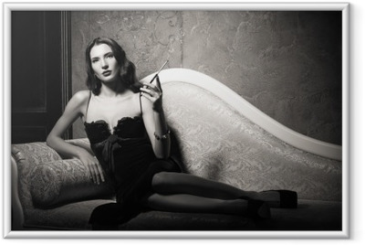 Film noir style: elegant young woman lying on sofa and smoking cigarette. Black and white Framed Poster