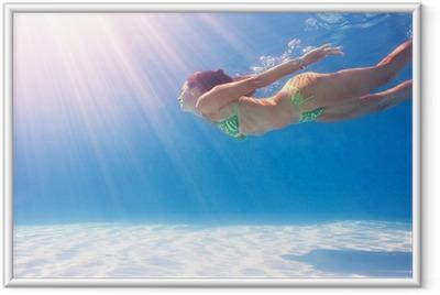 Innrammet plakat Kvinne svømmer under vann i et blått basseng.