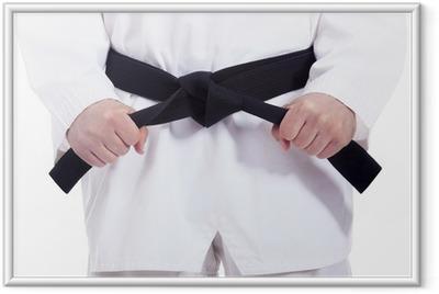 Poster en cadre Les arts martiaux homme attachant sa ceinture noire, isolé sur blanc