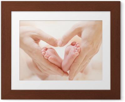 Tiny Newborn Baby's feet on female Heart Shaped hands closeup Framed Poster