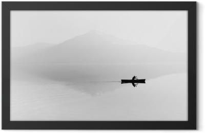 Fog over the lake. Silhouette of mountains in the background. The man floats in a boat with a paddle. Black and white Framed Poster