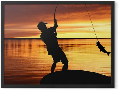 fisherman with a catching fish on sunrise background Framed Poster