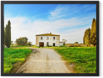 Old abandoned rural house, road and trees on sunset.Tuscany, Ita Framed Poster