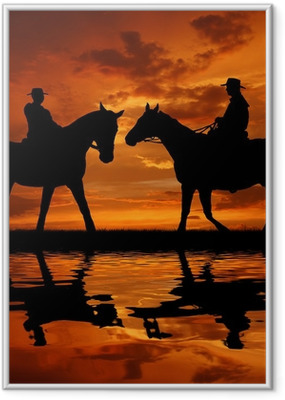 Silhouette cowboys with horses in the sunset Framed Poster