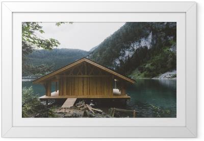 Innrammet plakat Vedhus på innsjø med fjell og trær
