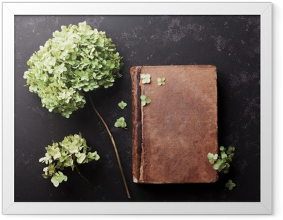 Still life with old book and dried flowers hydrangea on black vintage table top view. Flat lay styling. Framed Poster