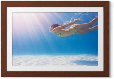 Póster com Moldura Woman swimming underwater in a blue pool.