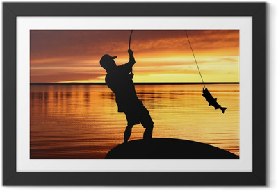 Póster com Moldura fisherman with a catching fish on sunrise background