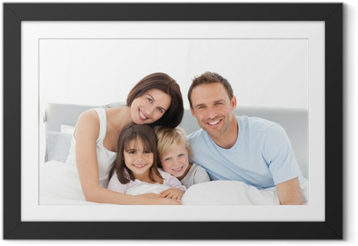 Póster com Moldura Portrait of a happy family sitting on the bed